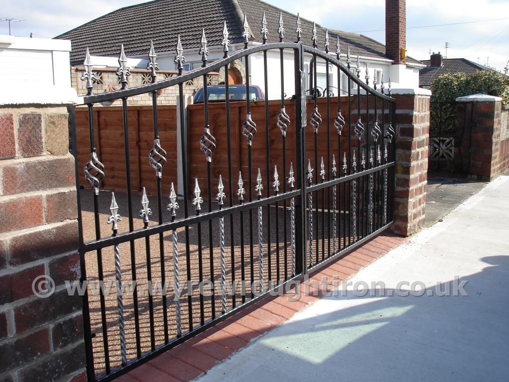 Double arch gates with railheads, cages twists and twisted bars. Powder coated in black and fitted to a property near Stannah, Poulton-le-Fylde.