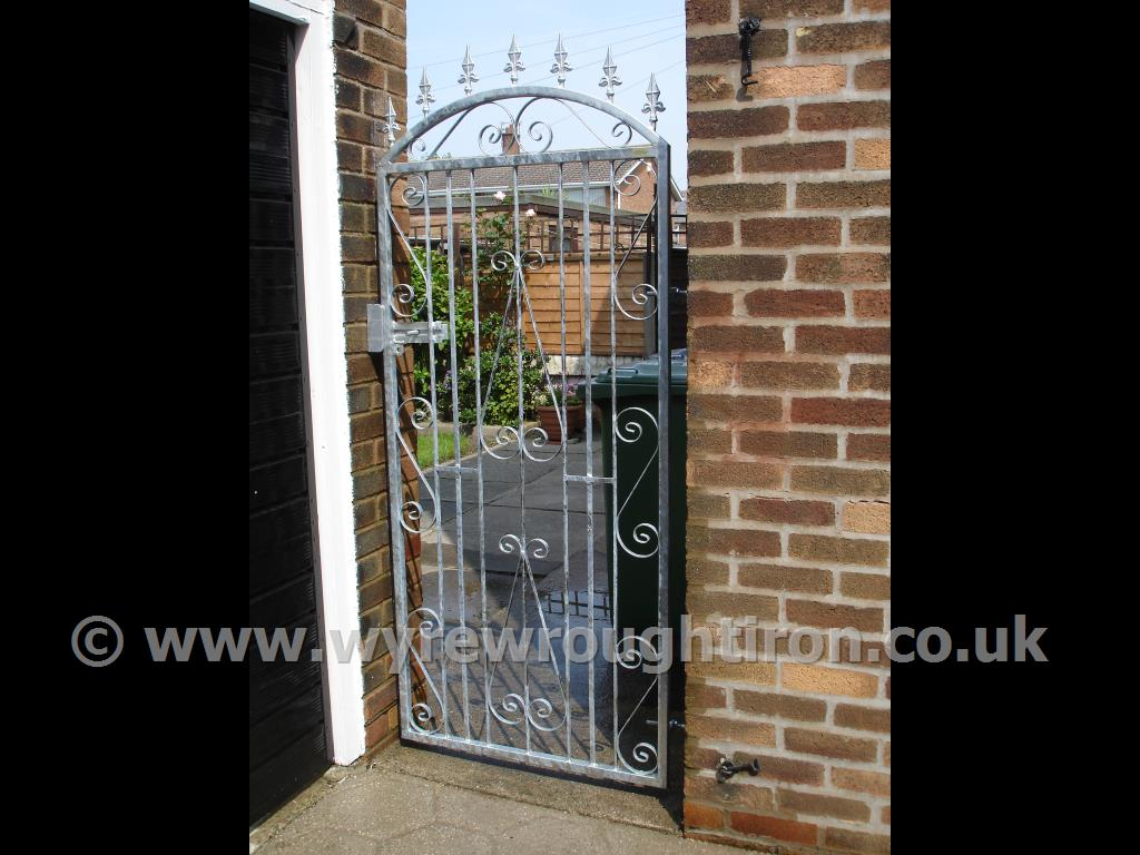 Tall single gate in galvanised finish with slide bolt for a padlock to secure this rear garden in Layton, Blackpool. Spiked finials add extra security as something uncomfortable to climb over.