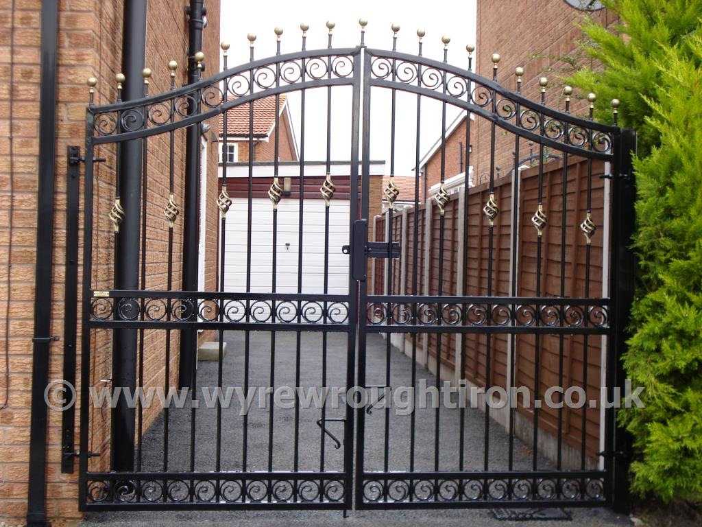 Tall double arched gates with railheads, scrolled tail circles, black powder coating and gold finish created for Lytham St Annes customer.