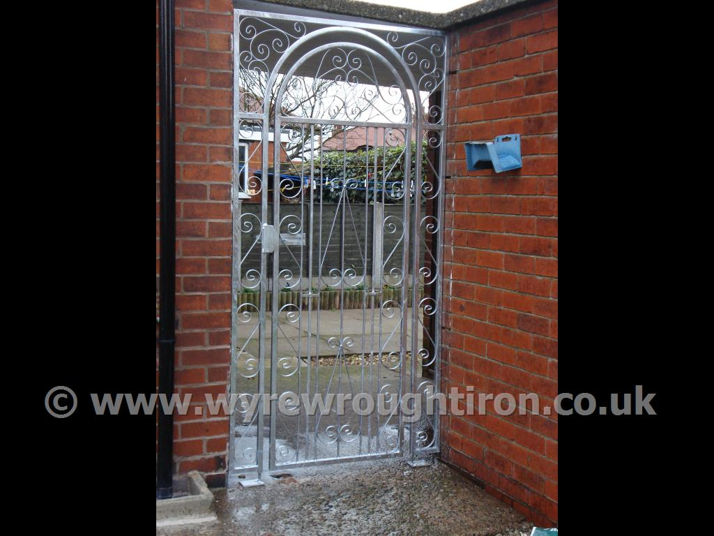 Tall single arched gate with scrollwork design, matching scrollwork frame and lockable slide bolt providing security for the rear garden. Fitted in Carleton, near Blackpool.