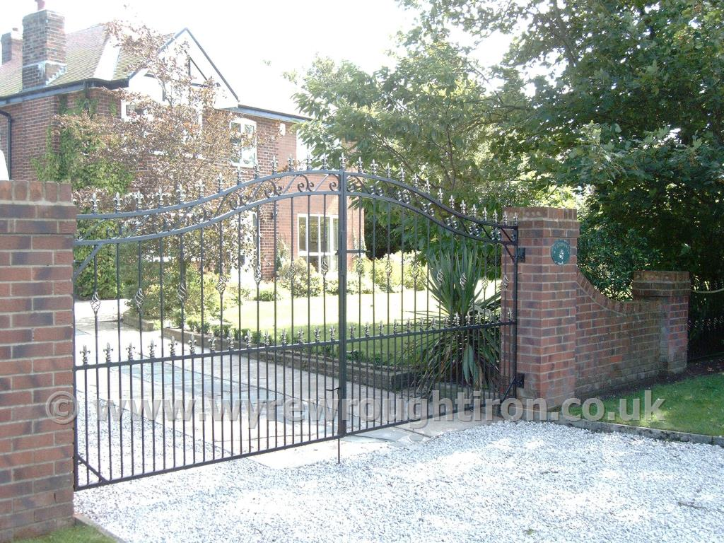 Imposing wide and tall double arched driveway gates with scrollwork, railheads, cage twists and black finish, fitted to a house in Hambleton, Over Wyre.